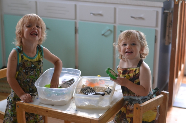 Flour and baby oil.  Who knew it would make 'sand' to occupy much time.  And cute aprons bought at a local craft fair!